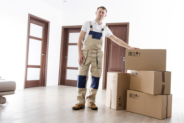 Relocation service man with cardboard box in room of apartment. Mover in home. Worker loader in uniform and many boxes in house