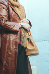 Woman wearing silver wristwatch and brown leather coat holding leather brown handbag