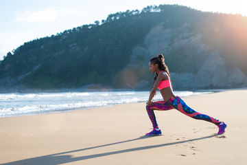 Fitness woman stretching legs or doing lunges at the beach. Black Female athlete doing relaxing exercise towards the sea.