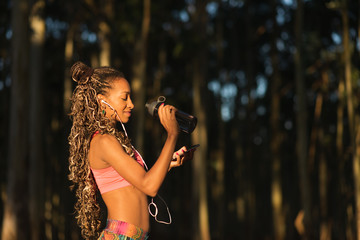 Side view of fitness brazilian sportswoman taking a break for drinking water and listening music on smart phone during outdoor workout. Black female athlete wearing earphones.