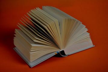 Open Book forming a fan on orange background