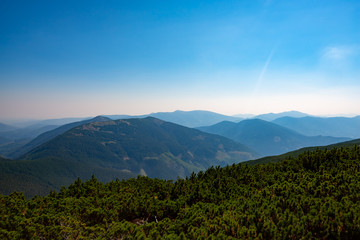 Wooded hills and green valleys under blue sky