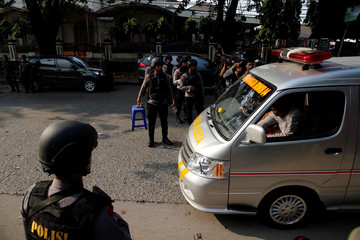 Policemen guard as an ambulance passes near the Mobile Police Brigade (Brimob) headquarters in Depok