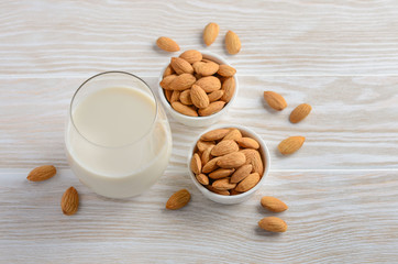 Almond milk and almonds on a white wooden background, selective focus