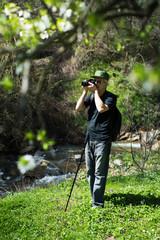 Senior man taking pictures on a hiking trip
