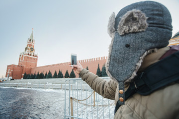 concept of travel. The tourist in a cap makes photos on his phone Moscow landscape with the Kremlin Intercession Cathedral on Red Square, Russia.