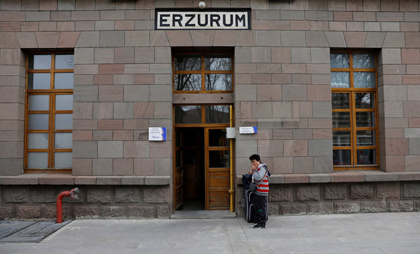 A passenger smokes at the entrance of the main train station in the eastern Anatolian city of Erzurum