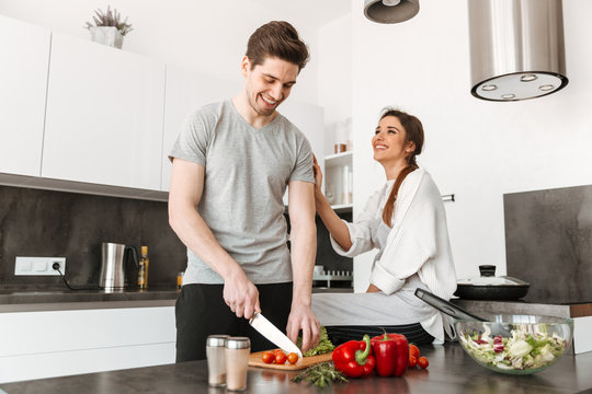 Portrait of a joyful young couple cooking together