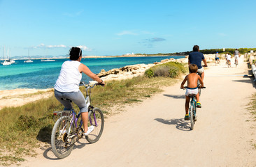 Ibiza, Spain - October 5, 2017 : View of road with car and bicyclist riding on pear. Big green palm tree on Ibiza and Formentera island beach. Summer holidays and free time at sunny weather near sea.