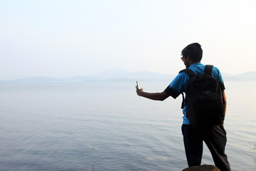 A man takes selfie photo in the morning near lake in india