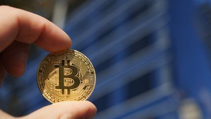 Hand holding Bitcoin gold coin and the business building in the background