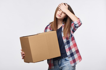 Delivery, relocation and unpacking problems. Discontent young woman holding cardboard box with hand on head
