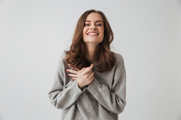 Laughing brunette woman in sweater posing and looking at camera