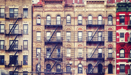 Vintage stylized picture of old buildings with fire escapes, one of New York City symbols, USA.