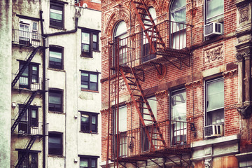 Retro stylized picture of old buildings with fire escapes, one of New York City symbols, USA.