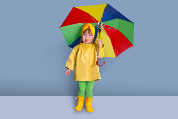 Happy funny child with color umbrella posing on wall background.