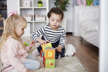 Two little girls playing with toy blocks on carpet at home