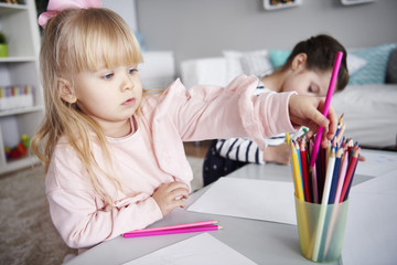 Portrait of little girl drawing with coloured pencils in the living room