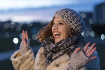 Woman very happy with bokeh lights in background and winter clothing.Jaen, Spain.