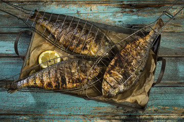 Grilled fish served on a tray against wooden background