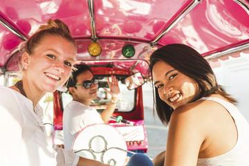 Thailand, Bangkok, portrait of smiling friends riding tuk tuk