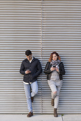 Young couple looking phones ignoring one to other in a reflection society. Jaen, Spain.