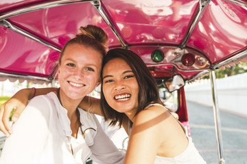 Thailand, Bangkok, portrait of two happy two friends riding tuk tuk