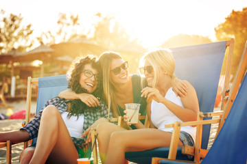 Group of young casual female friends sitting on beach on sunbeds,hangout and toasting with drink.
