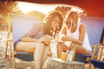 Two young casual female friends sitting on beach on sunbeds,hangout and relaxing.Using  smart phone.