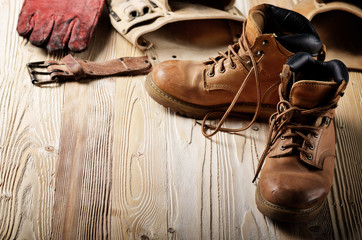 Yellow leather used work boots with tool belt and protective gloves on wooden background closeup. Place for text Wall mural