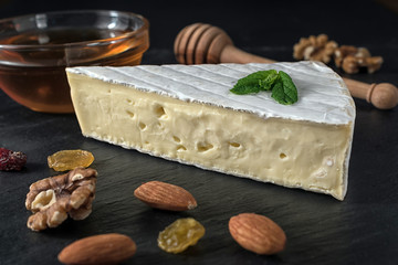 Fresh Brie cheese on black stone board with nuts, honey and herbs.