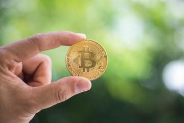 man's hand holding golden Bitcoin.