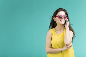 Beautiful smiling brunette girl wears yellow t-shirt and sunglasses talking happily by phone before blue background
