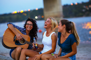 Group of young female friends sitting on the river beach ,singing and playing guitar.Joying in summer evening .