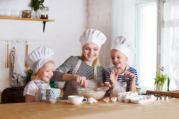 mother and two little childrens are cooking cookies and having fun in the kitchen.