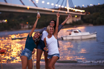 Group of young female friends relaxing on the river beach ,singing and playing guitar.Joying in summer evening .