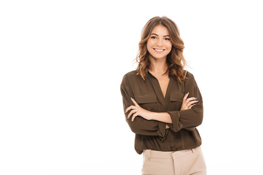 Portrait of a smiling young woman standing with arms folded