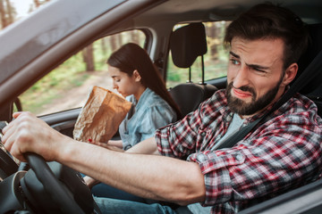 Couple is driving in car. Girl feels sick. She is vomiting into paper bag. Guy feels disgustion. He is not looking at girl.