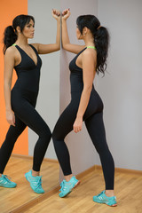 Attractive brunette fit and sporty woman doing exercises near the mirror, wearing stylish sportswear. Fitness gym, indoors