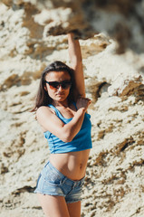 beautiful sporty girl with perfect figure in denim shorts by the sea