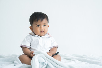 cute little asian boy sitting on soft blanket