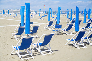 Deckchairs and sunshade on the beach at the mediterranean seaside. Summer, holidays, vacation,travel concept.