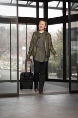 Frau mit Koffer läuft durch Tür vom Hotel, Ankunft für eine Übernachtung