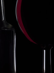 Glass of wine and empty bottle on the black background