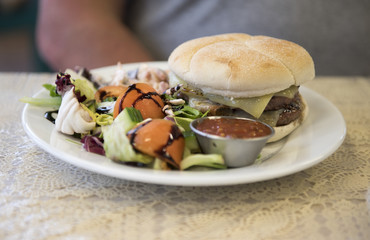 Cheese burger with a side salad on a white plate