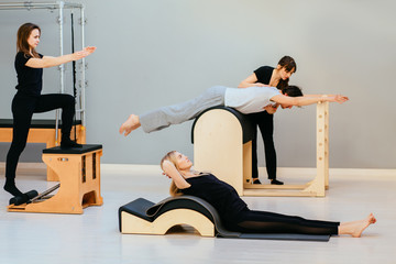 Group of sporty three people are working out pilates exercises with instructor on special equipment in eco modern studio interior. Fitness, sport, training and people concept.