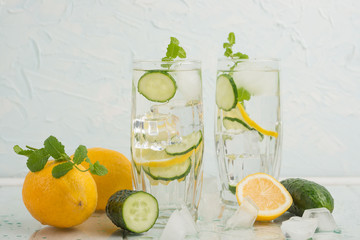 Rejuvenating drink, cocktail, tea, water with lemon, inbet, mint, cucumber in clear glass on a white background. Improvement and purification of the body. Detox.