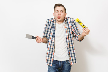Young shocked handsome man in casual clothes holding putty knife and building bubble spirit level isolated on white background. Instruments for renovation apartment room. Repair home concept.