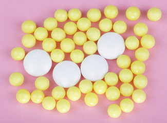 yellow vitamins on pink background