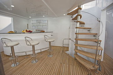 Wooden staircase and bar on sundeck of luxury yacht